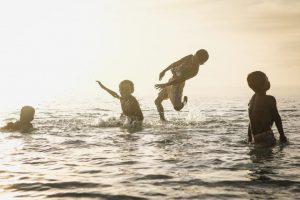 ילדים משחקים בחדווה בים. חופש בתוך פעילויות