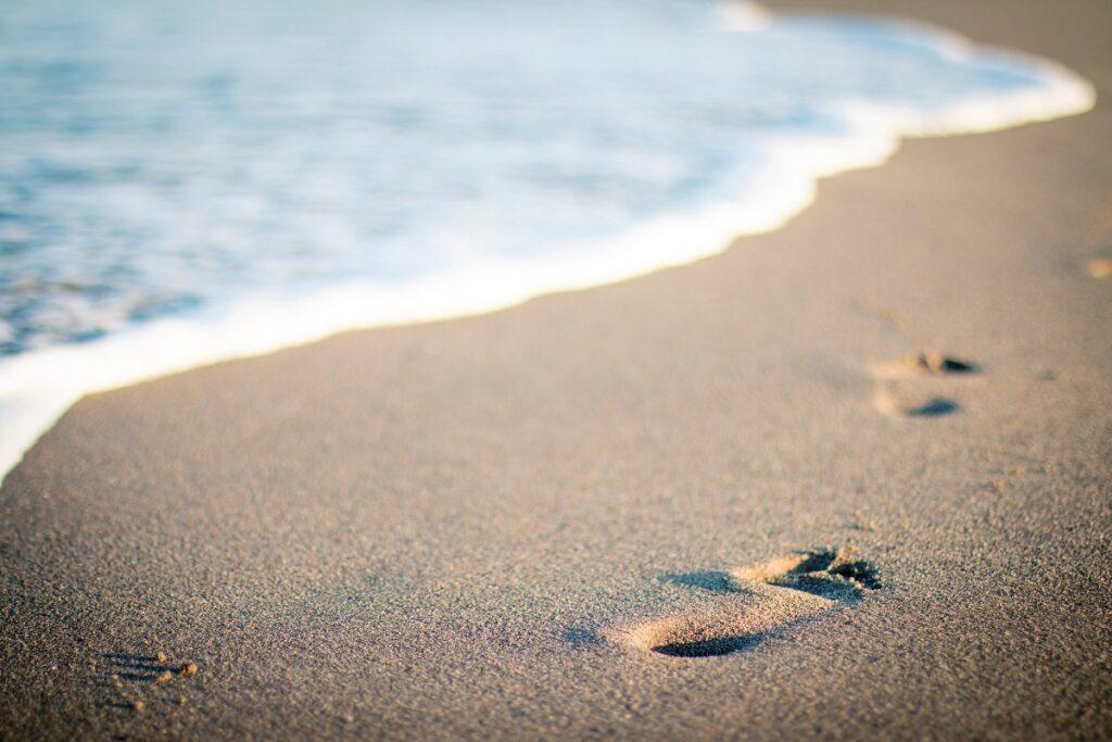 עקבות צעדים על החוף. צעד קדימה מתנועת החיים